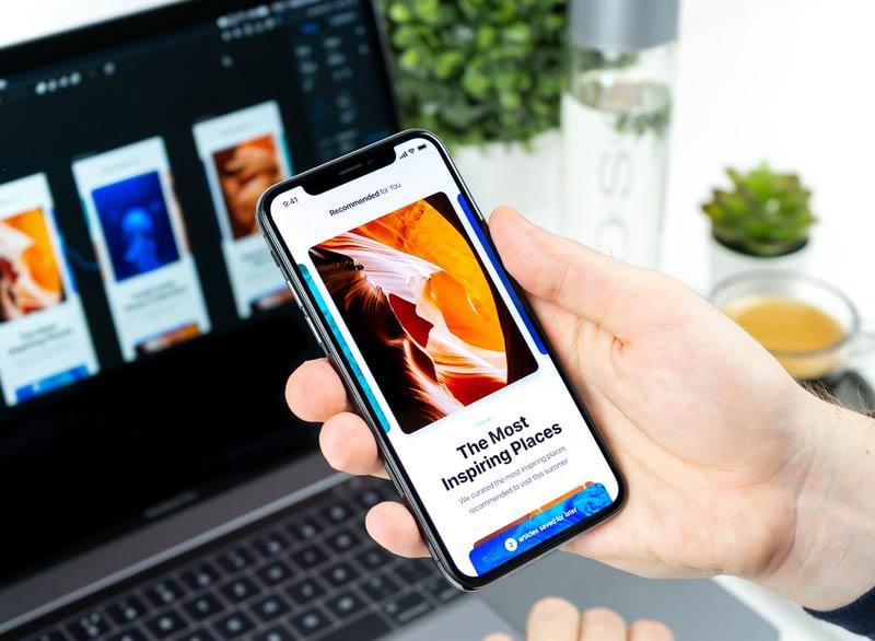 personne en train de ternir un téléphone dans sa main devant un ordinateur mac